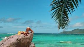 Le modèle se bronze sur la roche de plage de lagune. Photo libre de droits