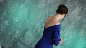 Le modèle sexy élégant de jeune fille se tient dans une longue robe bleue banque de vidéos