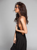 Le modèle sexy de femme dresed dans la robe noire et les longues bottes dans le studio image stock