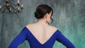 Le mod?le sexy ?l?gant de jeune fille se tient dans une longue robe bleue banque de vidéos