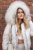 Le mod?le utilise un dessus blanc et une veste blanche avec un capot volumineux photos stock