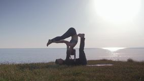 Le mode de vie de bien-être, paire de yoga fait des exercices dans le pré appréciant la nature, air frais sur le fond de la mer banque de vidéos