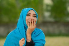 Le mode de vie a isolé le portrait de la jeune belle et heureuse femme asiatique dans rire principal musulman d'écharpe de hijab  photographie stock libre de droits