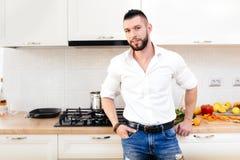 Le mode de vie moderne, homme s'est habillé avec la chemise et les jeans élégants faisant cuire et préparant la nourriture dans l photo libre de droits