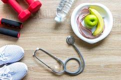 Le mode de vie sain pour des femmes suivent un régime avec l'équipement de sport, les espadrilles, la bande de mesure, les pommes Photographie stock libre de droits