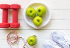 Le mode de vie sain pour des femmes suivent un régime avec l'équipement de sport, les espadrilles, la bande de mesure, les pommes Images stock