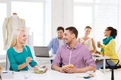 Le modeformgivare som har lunch på kontoret Royaltyfria Bilder