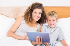 Le moder- och sonsammanträde på säng med minnestavlaPC royaltyfria bilder