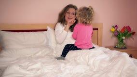 Le modermamman och hennes gulliga dotterflicka ha gyckel i säng stock video