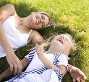 Le modern och den lilla dottern på naturen. Lyckligt folk utomhus arkivfoton