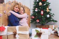 Le modern och dottern med julpynt och gåvor Arkivfoton