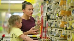 Le modern och dottern på supermarket En dotter hjälper hennes moder att välja en tejp Cutie dotter stock video