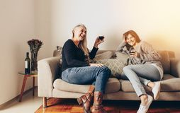 Le modern och dottern som kopplar av på en soffa och att dricka seger royaltyfri bild
