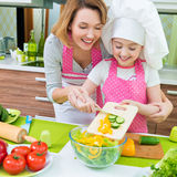 Le modern och dottern som lagar mat en sallad royaltyfria foton