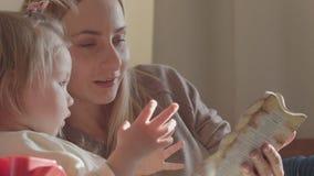 Le modern och dottern som tillsammans läser en bok i vardagsrummet stock video