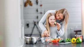 Le modern och flickan som förbereder sallad i en bunke i ett kök stock video