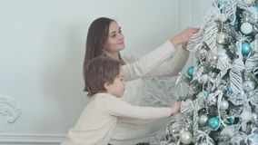 Le modern och hennes son som dekorerar julgranen i vardagsrummet royaltyfria bilder