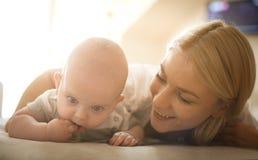 Le modern på säng med hennes behandla som ett barn pojken close upp fotografering för bildbyråer