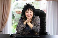 Le moget kvinnasammanträde på det svarta träskrivbordet Arkivfoton