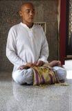 Le moine bouddhiste dans l'habitude de méditations se reflète Photographie stock libre de droits