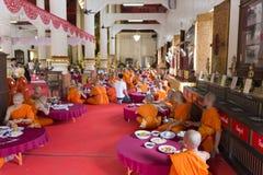 Le moine bouddhiste mangent le déjeuner dans le temple asiatique Image libre de droits