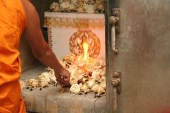 Le moine bouddhiste a mis les lumières sur le cercueil Images stock