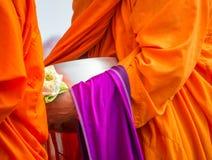 Le moine bouddhiste tenant l'aumône roulent et la fleur de lotus Photographie stock
