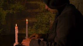 Le moine caicasian adulte s'asseyant à la table la nuit, homme a lu le livre la nuit avec des bougies s'allument Glissière de liv banque de vidéos