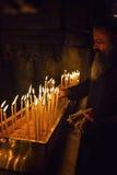 Le moine met des bougies dans l'église Photos libres de droits
