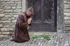 Le moine priant devant la porte du ` s de monastère Photographie stock