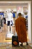 Le moine se tient devant le magasin d'Uniqlo dans l'aéroport de Changi Image libre de droits