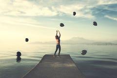 Le moment surréaliste, femme essaye à prendre les ballons noirs qui pleuvoir du ciel photographie stock