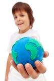Le monde dans ma main - jeune garçon tenant le globe de la terre Image stock