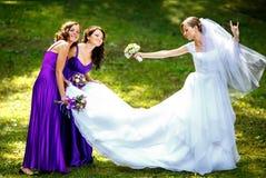 Le monde de la roche de jeune mariée posant avec des demoiselles d'honneur en parc Photos libres de droits