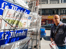 Le Monde reporting handover ceremony presidential inauguration o. PARIS, FRANCE - MAY 15, 2017: Black ethnicity man buying Le monde newspaper reporting handover Stock Photo
