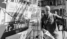 Le Monde reporting handover ceremony presidential inauguration o. PARIS, FRANCE - MAY 15, 2017: Black ethnicity man buying Le monde newspaper reporting handover Royalty Free Stock Photo