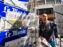 Le Monde reporting handover ceremony presidential inauguration o. PARIS, FRANCE - MAY 15, 2017: Black ethnicity man buying Le monde newspaper reporting handover Stock Photos