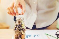 Le monete delle maniglie hanno disposto su un mucchio di soldi di risparmio sulla tavola con il concetto di affari del tramonto l fotografie stock libere da diritti