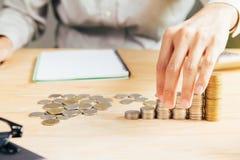 Le monete delle maniglie hanno disposto su un mucchio di soldi sulla tavola con il tramonto leggero Concetto di affari immagine stock libera da diritti