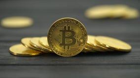 Le monete di oro di Bitcoin si trovano in mucchi sulla tavola Fine in su archivi video