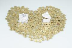 Le monete di oro come cuore a forma di hanno contenitore di regalo ed alloggiano Fotografie Stock Libere da Diritti