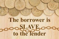 Le monete di oro con testo il prestito è schiavo al prestatore Fotografia Stock Libera da Diritti