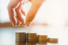 Le monete di oro sulla tavola con raccolgono a mano su immagini stock