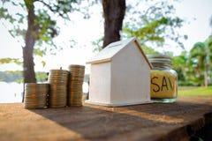 Le monete disposte sul pavimento di legno, risparmiano i soldi per preparano in futuro ed alloggiano Immagine Stock