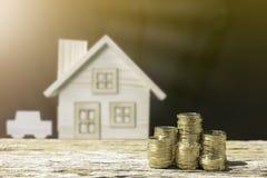 Le monete ed il fondo della sfuocatura della casa mostrano i soldi di risparmio fotografie stock libere da diritti