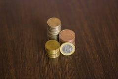 Le monete impilano su fondo di legno Fuoco su priorità alta con il fondo della sfuocatura Fotografia Stock