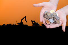 Le monete in mani sulla siluetta dell'industria abbelliscono il fondo Fotografia Stock