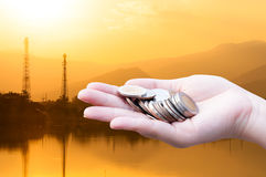 Le monete in mani sulla siluetta dell'industria abbelliscono il fondo, la carità del contributo finanziario del fondo di investim Immagini Stock