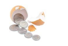 Le monete/soldi vengono dall'uovo della crepa su fondo bianco isolato Fotografia Stock Libera da Diritti