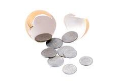 Le monete/soldi vengono dall'uovo della crepa su fondo bianco isolato Fotografie Stock